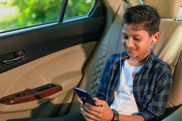Mignon enfant indien assis dans la voiture et à l'aide de gadget de téléphone intelligent et casque
