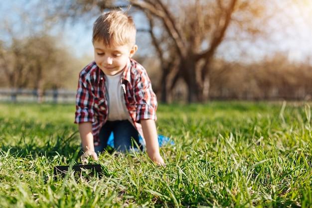 Mignon enfant souriant jouant dans l'herbe à l'extérieur dans une cour de maison de campagne familiale