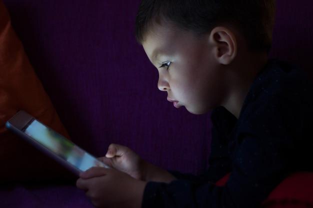 Mignon enfant avec tablette dans l'obscurité