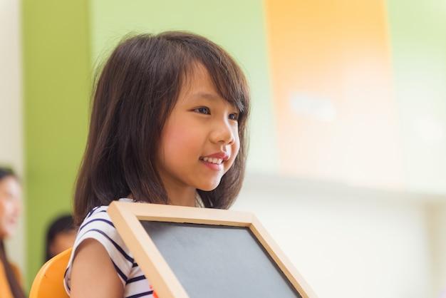Mignon fille asiatique tenant un tableau blanc avec un visage heureux dans la salle de classe de maternelle, un concept d'éducation à la maternelle, des images de style effet vintage.