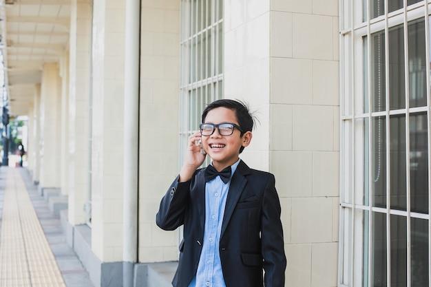 Mignon garçon asiatique portant un costume noir vintage et des lunettes parler au téléphone en souriant