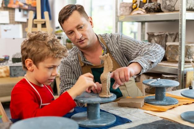 Mignon garçon assis près de son professeur sculptant petit animal d'argile