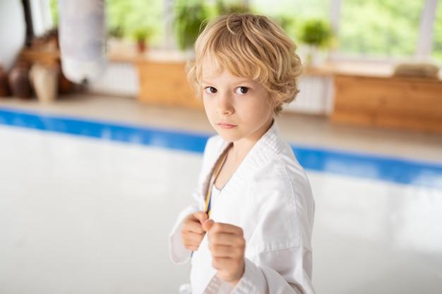 Mignon garçon aux yeux sombres portant un kimono blanc montrant ses poings