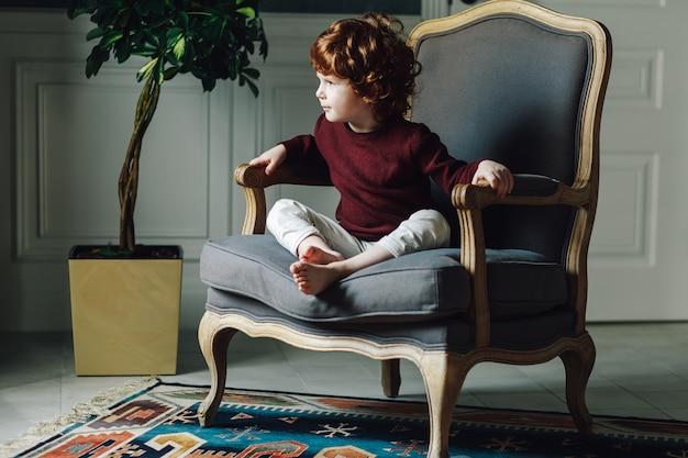 Mignon garçon bouclé assis détendu dans un fauteuil confortable et à la recherche de suite