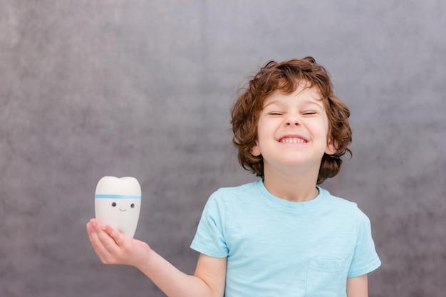 Mignon garçon bouclé tient la grosse dent et sourire sur le mur gris. le concept de la santé des enfants, la médecine.