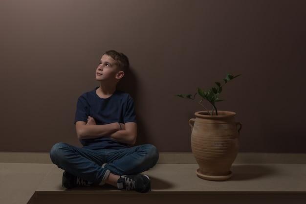 Mignon garçon élégant assis sur le sol près de la fleur dans un pot sur fond de mur marron.
