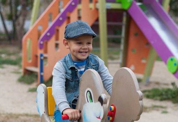 Mignon garçon européen sur l'aire de jeux dans la cour sur une balançoire en été