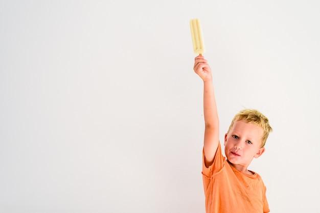 Mignon garçon mangeant une glace en fond blanc.