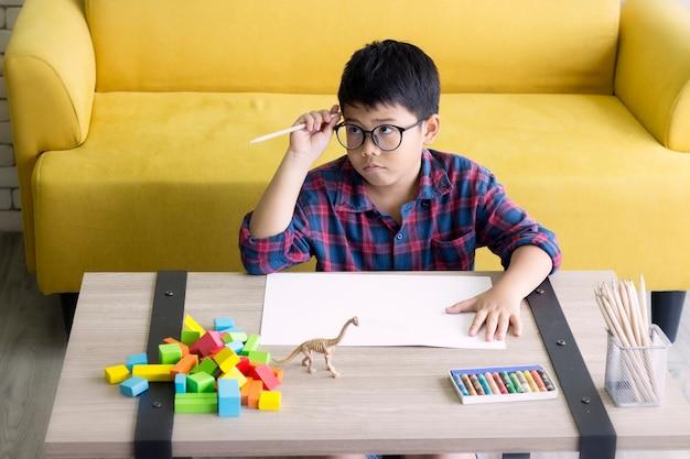 Le mignon garçon réfléchit en faisant ses devoirs, assis à la maison.