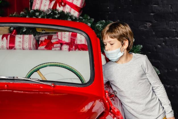 Mignon garçon sérieux dans des masques médicaux près de la voiture de noël.
