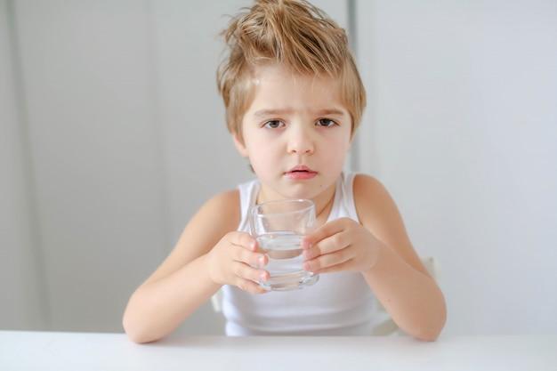 Mignon garçon souriant avec verre d'eau isolé sur fond blanc