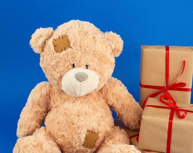 Mignon gros ours en peluche beige détient une boîte brune avec un ruban rouge