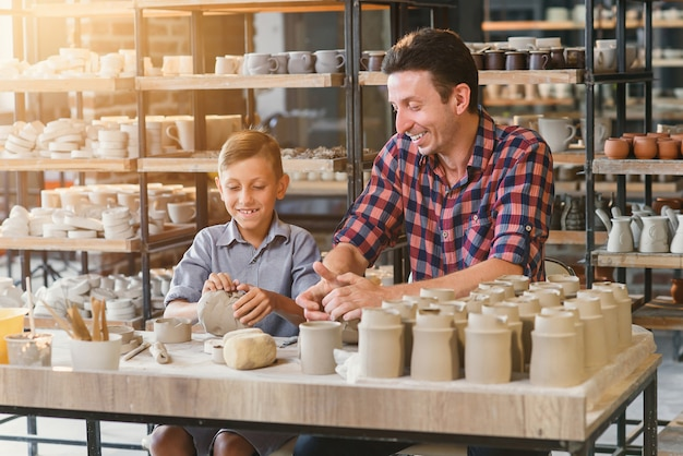 Mignon homme d'âge moyen avec son petit fils s'amusant dans la poterie.