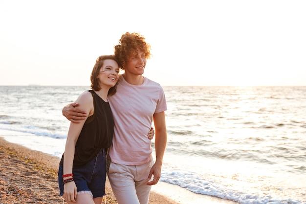 Mignon jeune couple d'amoureux heureux étreignant à l'extérieur sur la plage