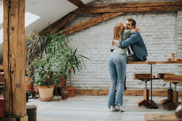 Mignon, jeune couple, étreindre, pendant, cuisine, dans, leur, cuisine