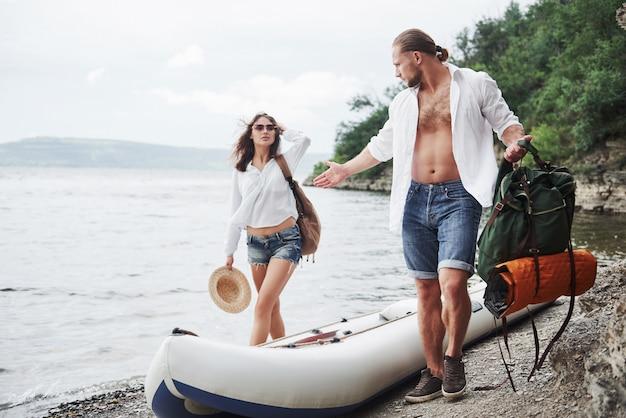 Mignon jeune et couple sur la rivière. un gars et une femme avec des sacs à dos voyagent en bateau. concept d'été voyageur