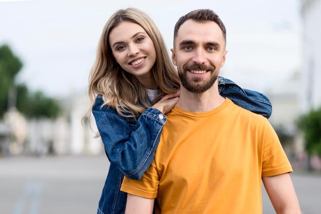 Mignon jeune couple sourire à la caméra