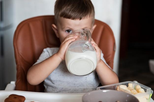 Mignon jeune garçon buvant du lait