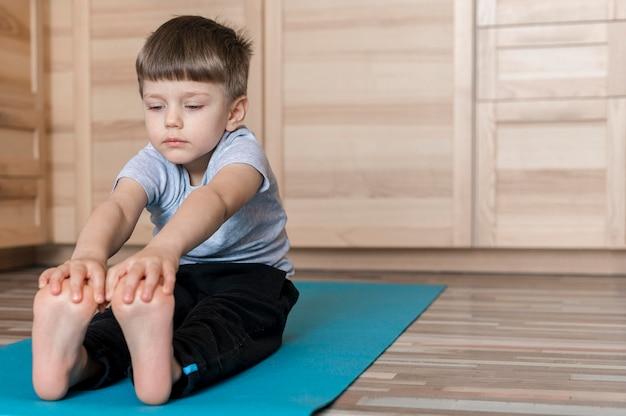 Mignon jeune garçon exerçant sur un tapis de yoga