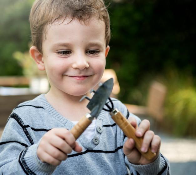 Mignon jeune garçon jouant avec des outils de jardinage