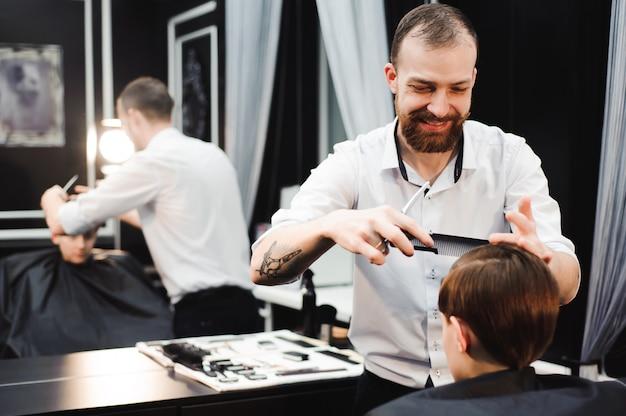 Mignon jeune garçon obtenant une coupe de cheveux dans un salon de coiffure.