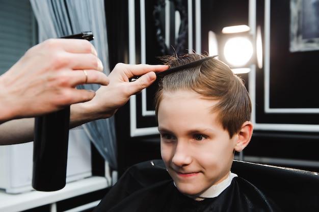 Un mignon jeune garçon se coupe les cheveux