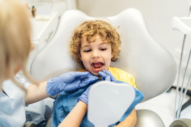 Mignon jeune garçon en visite chez le dentiste, ayant ses dents vérifiées par une femme dentiste au cabinet dentaire.
