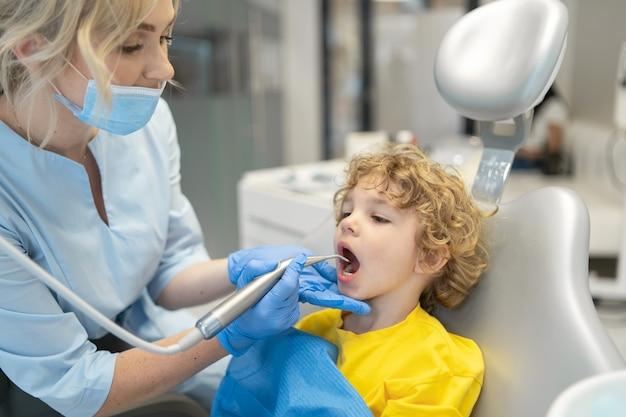 Mignon jeune garçon en visite chez le dentiste et ayant ses dents vérifiées par une femme dentiste en cabinet dentaire