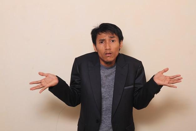 Mignon jeune homme asiatique montre que je ne sais pas geste avec haussement d'épaules, portant un