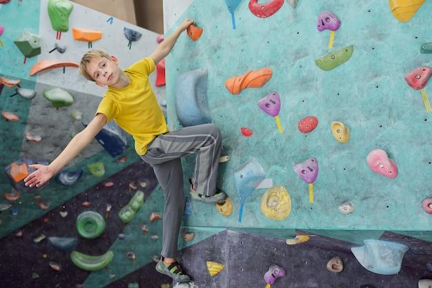 Mignon jeune en t-shirt jaune et pantalon gris vous regarde tout en tenant par petit rocher sur un mur d'escalade pendant l'exercice
