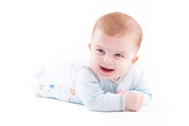 Mignon joli bébé garçon en pijama bleu se trouve sur le ventre