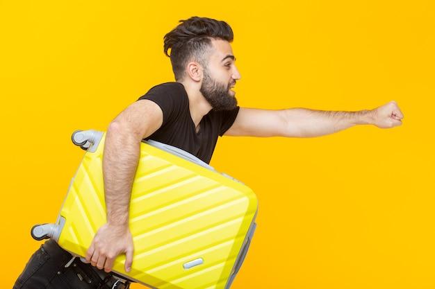 Mignon joli jeune homme avec une barbe tenant une valise jaune dans ses mains sur un mur jaune