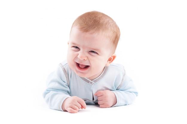 Mignon joli petit garçon en chemise bleue se trouve sur le ventre