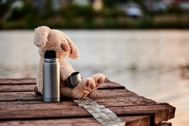Mignon lapin doux avec un thermos sur la jetée près du lac. espace de copie.