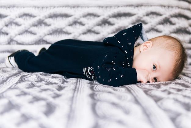 Mignon nouveau-né couché sur le ventre et regardant à travers ses doigts sur fond gris blanc, selective focus