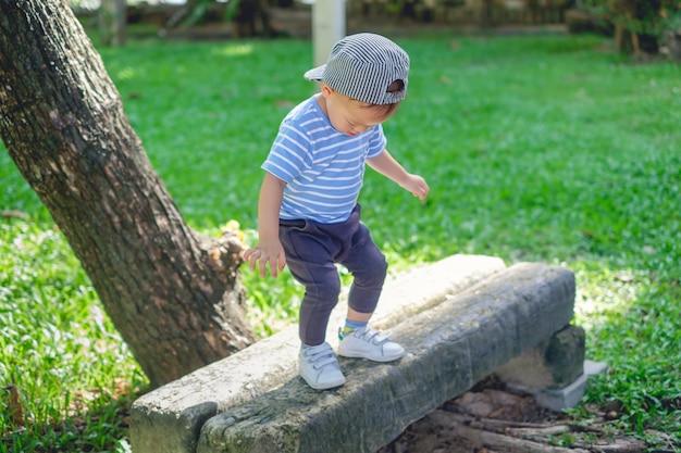 Mignon petit asiatique 18 mois, 1 an enfant en bas âge bébé garçon enfant marchant sur la poutre d'équilibre dans le parc sur la nature en été, coordination physique, manuelle et oculaire, sensorielle, concept de développement des habiletés motrices