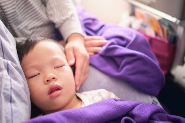 Mignon petit asiatique 3 ans bambin garçon enfant dormant dans l'avion, enfant dormant sur les genoux de la mère pendant le vol en avion, volant avec des enfants concept