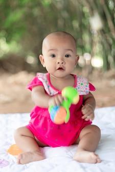 Mignon petit bébé asiatique assis et jouer avec bonheur