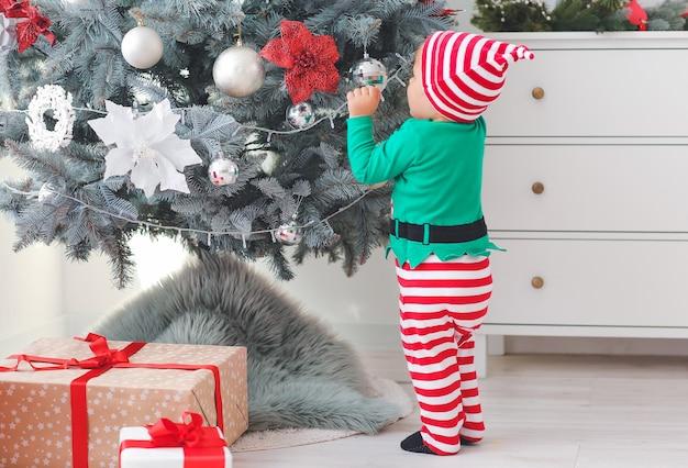 Mignon petit bébé en costume d'elfe près de l'arbre de noël à la maison