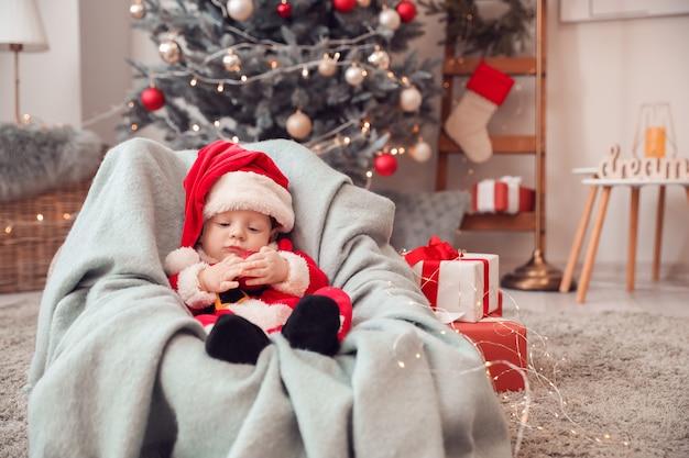 Mignon petit bébé en costume de père noël à la maison
