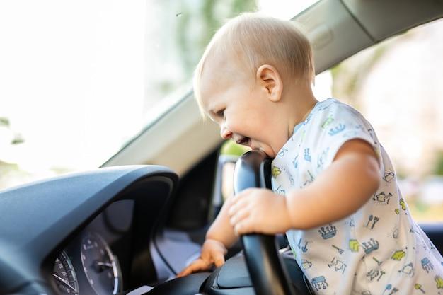 Mignon petit bébé garçon conduisant une grosse voiture, tenant le volant, souriant et impatient avec intérêt. jeu d'enfance et rêves. espace de copie