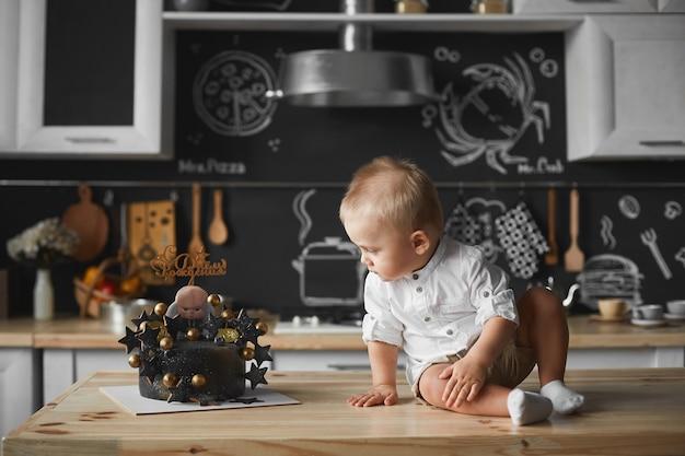 Mignon petit bébé garçon est assis sur la table à l'intérieur de la cuisine