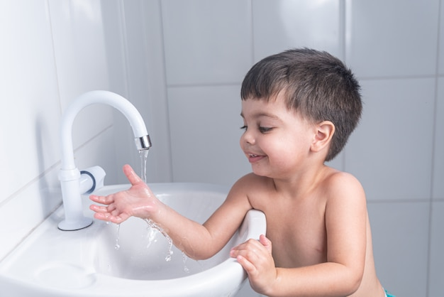 Mignon petit bébé garçon lavant la main dans le lavabo de la salle de bain