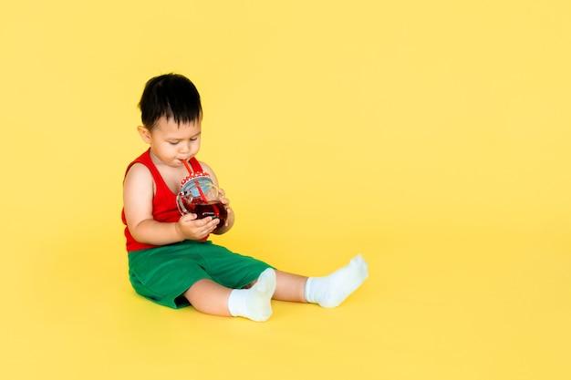 Mignon petit bébé garçon en t-shirt rouge et short vert avec une tasse de jus sur fond de couleur jaune