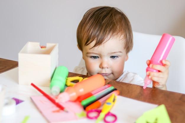 Mignon petit bébé garçon tenant de la peinture rose dans sa main en regardant les ciseaux sur la table. bricolage conc
