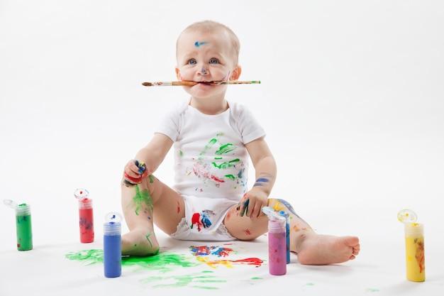 Mignon petit bébé peinture avec pinceau et peintures colorées sur blanc.
