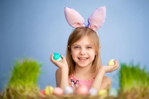 Mignon petit bébé porte des oreilles de lapin le jour de pâques. jolie petite fille avec des oeufs de pâques et de l'herbe verte. mur bleu