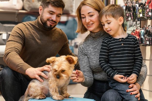 Mignon petit chien avec des propriétaires à l'animalerie