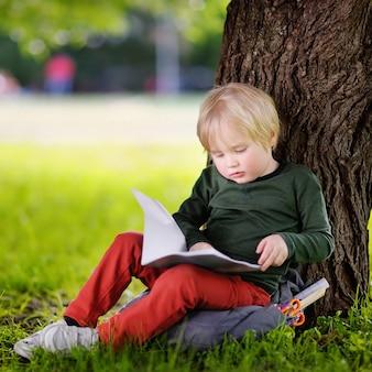 Mignon petit écolier assis sous un arbre et étudiant. retour au concept d'école.