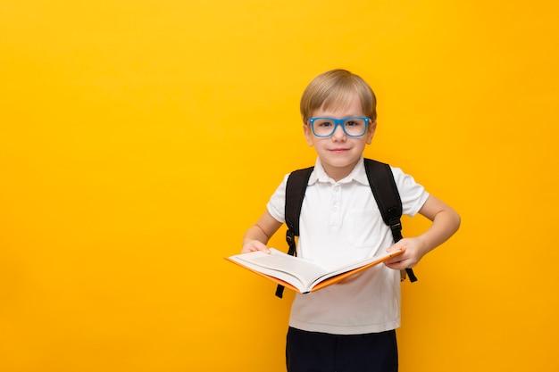 Mignon petit écolier dans des verres tenant le livre sur jaune